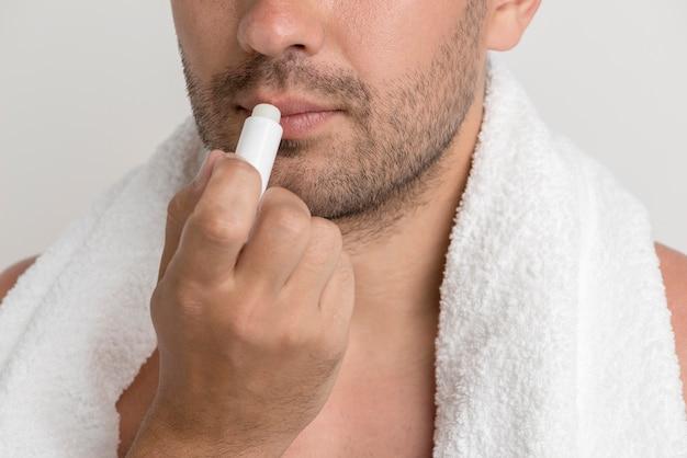 Junger stoppelmann mit dem weißen tuch, das balsam auf lippen aufträgt Kostenlose Fotos