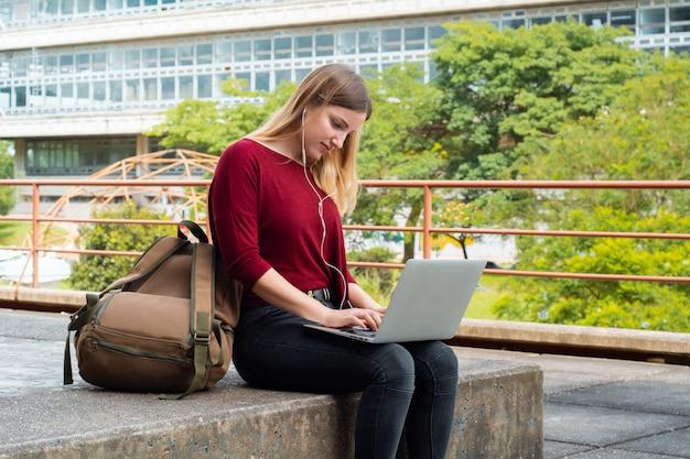Junger student, der draußen laptop verwendet. Premium Fotos