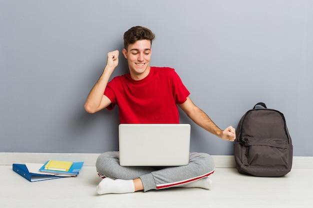 Junger studentenmann, der auf seinem hausboden hält einen laptop sitzt Premium Fotos