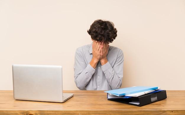Junger studentenmann mit einem laptop mit müdem und krankem ausdruck Premium Fotos