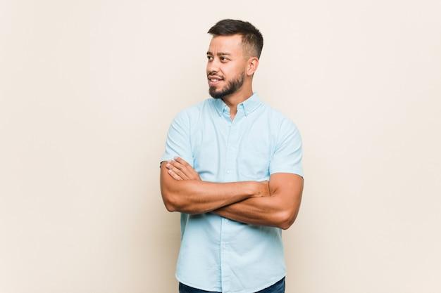 Junger südasiatischer mann, der mit den gekreuzten armen überzeugt lächelt. Premium Fotos