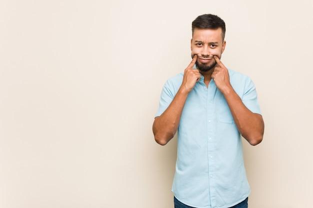 Junger südasiatischer mann, der zwischen zwei wahlen zweifelt. Premium Fotos