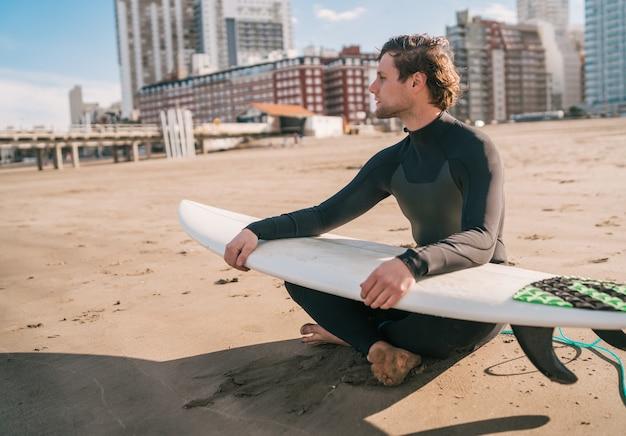 Junger surfer, der auf sandstrand sitzt und den ozean mit seinem surfbrett betrachtet. sport- und wassersportkonzept. Kostenlose Fotos