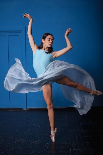 Junger tänzer des modernen balletts, der auf blau aufwirft Kostenlose Fotos