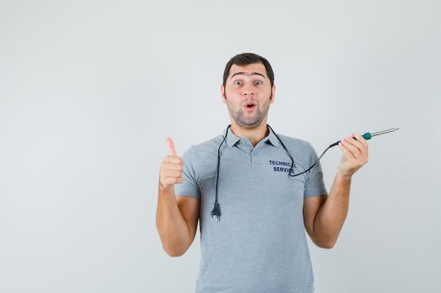 Junger techniker, der bohrer in einer hand hält, während daumen in grauer uniform zeigt und überrascht aussieht. Kostenlose Fotos