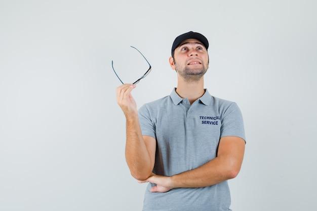 Junger techniker, der brille in grauer uniform hält und nachdenklich aussieht. Kostenlose Fotos