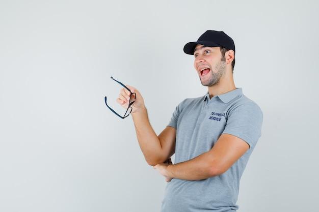 Junger techniker, der brille in grauer uniform hält und optimistisch schaut. Kostenlose Fotos