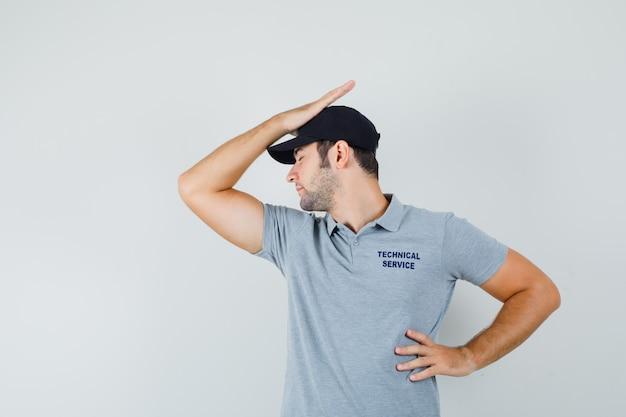 Junger techniker, der eine hand auf kopf, eine andere hand auf taille in grauer uniform hält und enttäuscht aussieht. Kostenlose Fotos