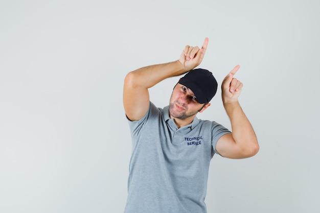 Junger techniker, der finger über kopf als stierhörner in grauer uniform hält und lustig aussieht. Kostenlose Fotos