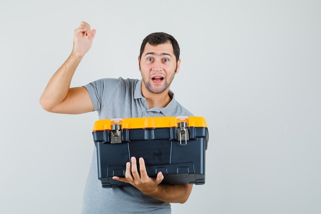 Junger techniker, der werkzeugkasten hält, während er seine eine hand in der grauen uniform hebt und überrascht aussieht. Kostenlose Fotos