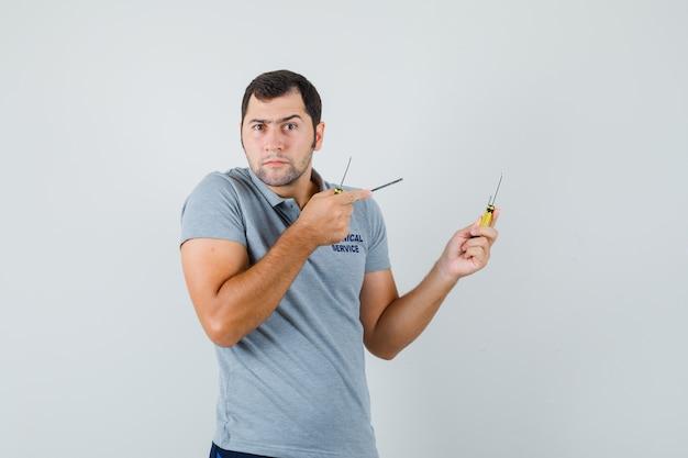 Junger techniker hält schraubendreher in beiden händen und zeigt auf sie in grauer uniform und sieht ernst aus. Kostenlose Fotos