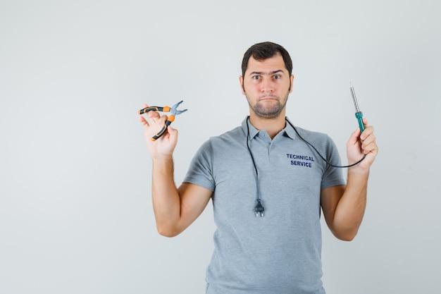 Junger techniker in grauer uniform hält bohrer in einer hand, zange in einer anderen hand und sieht ernst aus. Kostenlose Fotos