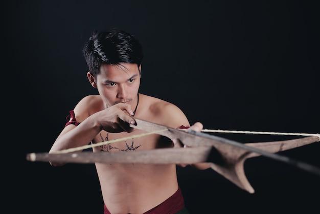 Junger thailand männlicher krieger, der in einer kämpfenden position mit einem schwert aufwirft Kostenlose Fotos