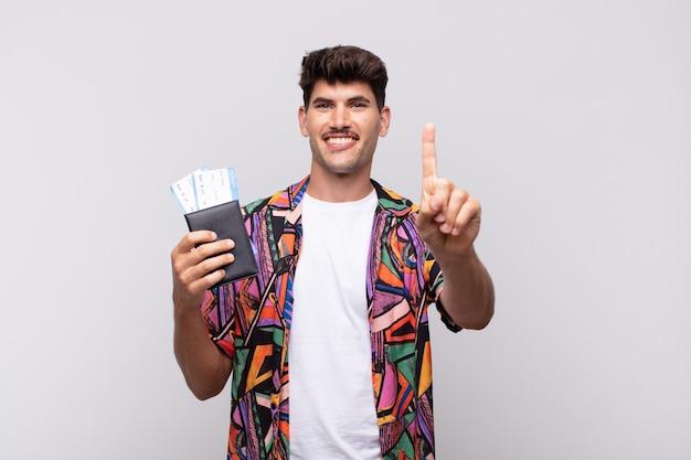 Junger tourist mit einem pass, der lächelt und freundlich aussieht, nummer eins oder zuerst mit der hand nach vorne zeigend, countdown Premium Fotos