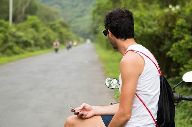Junger touristischer reiter mit sonnenbrille wartend auf sein motorrad und einen smartphone überprüfend Premium Fotos
