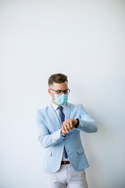 Junger und stilvoller geschäftsmann mit gesichtsmaske steht an der wand im büro und prüft die zeit Premium Fotos