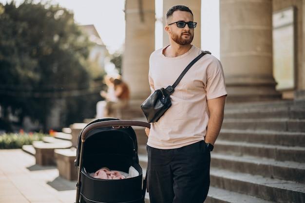 Junger vater, der mit seinem baby in einem kinderwagen hinausgeht Kostenlose Fotos