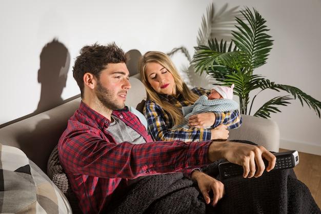 Junger vater, der während mutter mit dem babyschlafen fernsieht Kostenlose Fotos
