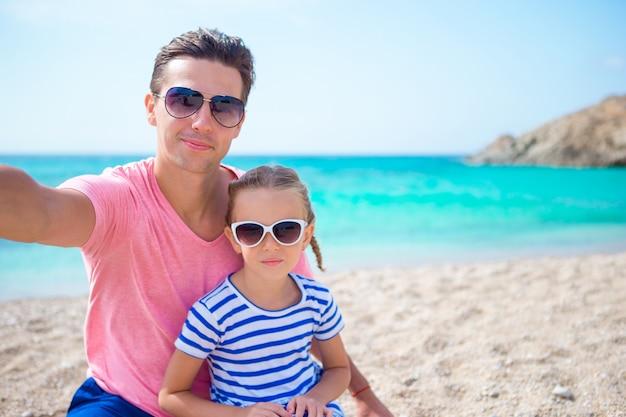 Junger vater und kleinkind, die selfie foto auf dem strand macht Premium Fotos