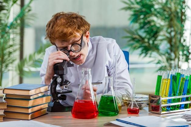 Junger verrückter chemiker, der im labor arbeitet Premium Fotos