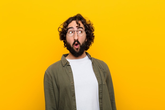 Junger verrückter mann, der entsetzt, glücklich, überrascht und überrascht sich fühlt und zur seite mit offenem mund gegen gelbe wand schaut Premium Fotos