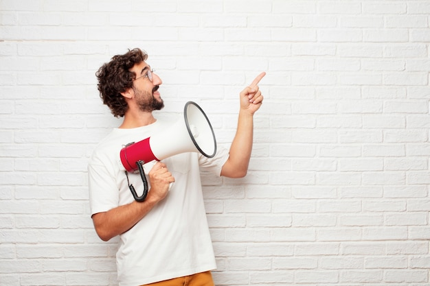 Junger verrückter mann mit einem megaphon gegen backsteinmauer. Premium Fotos