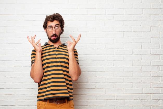 Junger verrückter oder dummer mann, der gefühle gegen backsteinmauerhintergrund gestikuliert und ausdrückt Premium Fotos