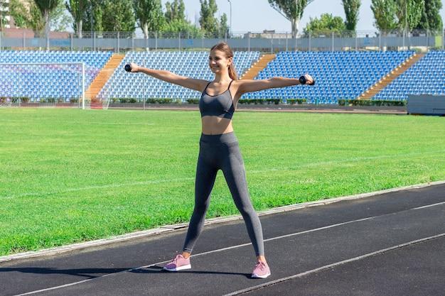 Junger weiblicher athlet mit den dummköpfen, die auf laufbahn im stadionsport- und -eignungskonzept ausdehnen und aufwärmen Premium Fotos