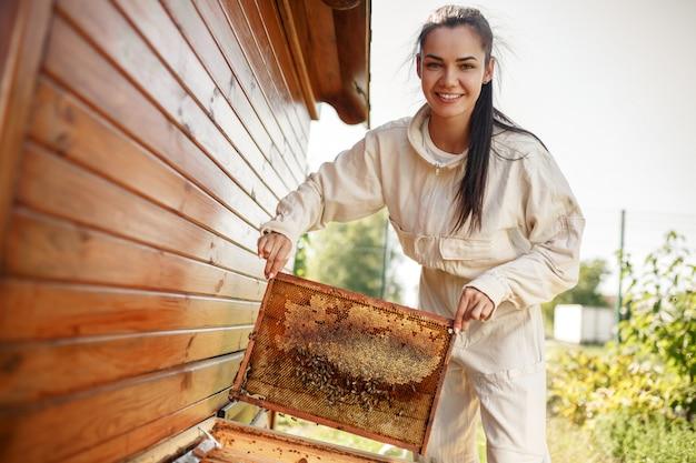 Junger weiblicher imker zieht vom bienenstock einen holzrahmen mit bienenwabe aus. Premium Fotos