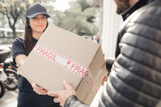 Junger weiblicher kurier, der paket zum mann liefert Kostenlose Fotos