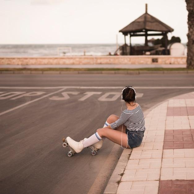 Junger weiblicher schlittschuhläufer, der auf hörender musik des bürgersteigs auf dem kopfhörer weg schaut sitzt Kostenlose Fotos