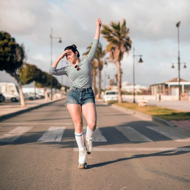 Junger weiblicher schlittschuhläufer mit ihrem arm hob tanzen auf straße an Kostenlose Fotos