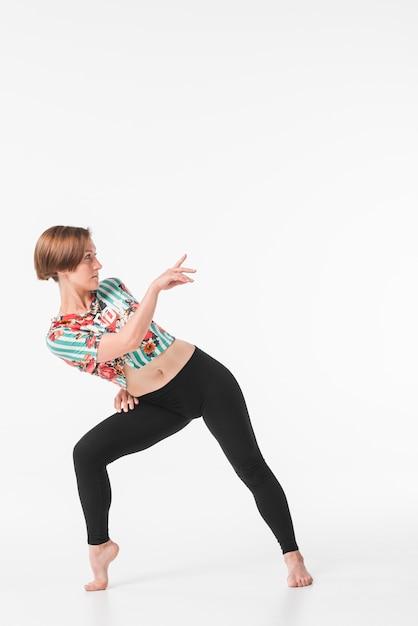 Junger weiblicher tänzer, der gegen weißen hintergrund aufwirft Kostenlose Fotos
