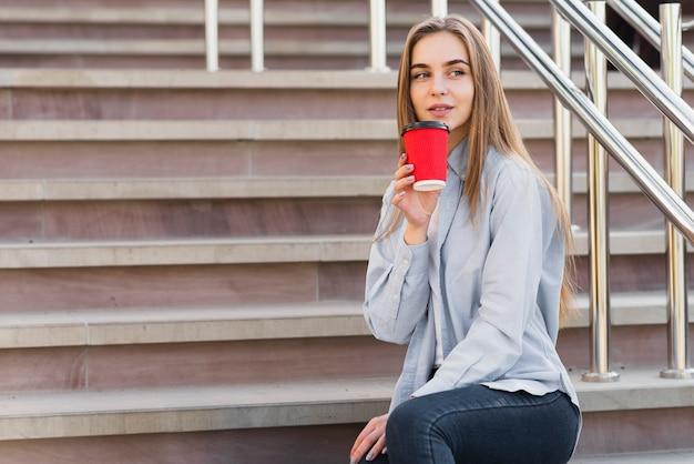 Junger weiblicher trinkender kaffee der seitenansicht im freien Kostenlose Fotos