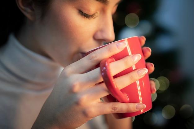 Junger weiblicher trinkender tee der seitenansicht Kostenlose Fotos