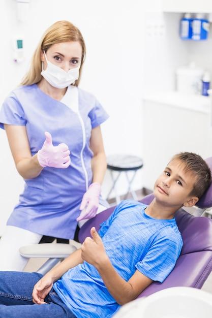 Junger weiblicher zahnarzt und junge, die oben daumen in der klinik gestikuliert Kostenlose Fotos