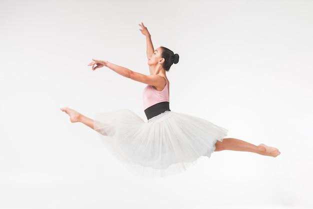 Junger würdevoller weiblicher balletttänzer, der gegen weißen hintergrund springt Kostenlose Fotos