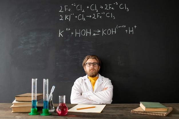 Junger zeitgenössischer chemielehrer im weißmantel, der seine arme auf der brust während des online-unterrichts an der tafel mit chemischen formeln kreuzt Premium Fotos