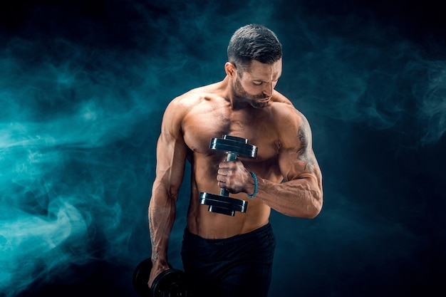 Junger zerrissener mannbodybuilder mit der perfekten abs, schultern, bizeps, trizeps und kasten, die mit einem dummkopf aufwerfen Premium Fotos