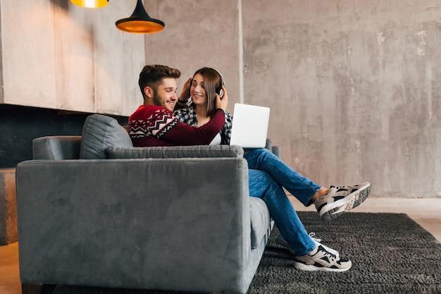 Junger ziemlich glücklicher lächelnder mann und frau sitzen zu hause im winter, suchen im laptop, hören kopfhörer, studenten, die online studieren, paar auf freizeit zusammen, Kostenlose Fotos