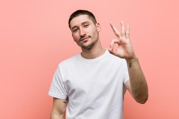 Junger zufälliger mann nett und überzeugt, okaygeste zeigend. Premium Fotos