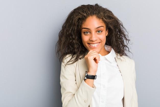 Junges afroamerikanergeschäftsfraulächeln glücklich und überzeugt, uching kinn mit der hand. Premium Fotos