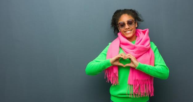 Junges afroamerikanermädchen mit den blauen augen, die eine herzform mit den händen tun Premium Fotos