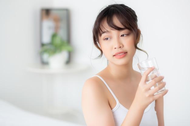 Junges asiatisches frauenlächeln des schönen porträts und trinkwasserglas mit frischem und reinem für diät Premium Fotos