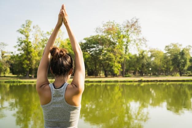 Junges asiatisches frauenyoga draußen halten ruhig und meditieren beim üben von yoga Kostenlose Fotos