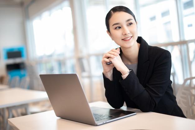 Junges asiatisches geschäftsmädchen, das mit laptop im kaffeehauscafé arbeitet, lächelnder blick weg. Premium Fotos