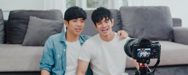 Junges asiatisches homosexuelles paarinfluencer-paar vlog zu hause. die jugendlich koreanischen glücklichen lgbtq-männer entspannen sich spaß unter verwendung des kameraaufzeichnungs-vlog-video-uploads in social media beim lügensofa im wohnzimmer am haus. Kostenlose Fotos