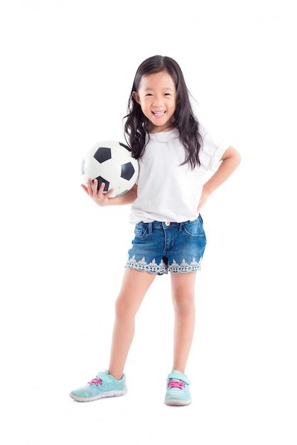 Junges asiatisches mädchen, das ball und lächeln über weißem hintergrund hält Premium Fotos
