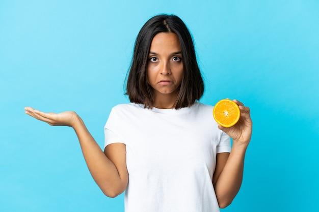 Junges asiatisches mädchen, das eine orange auf blau hält, die zweifel beim erhöhen der hände hat Premium Fotos