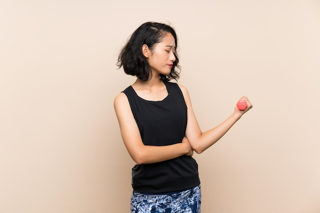 Junges asiatisches mädchen, das gewichtheben über lokalisierter wand mit traurigem ausdruck macht Premium Fotos